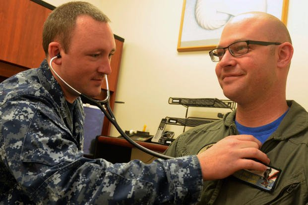 Hospital Corpsman 2nd Class Scott Henry monitors Naval Aircrewman Mechanical 1st Class David Gilbert's heart at Naval Hospital Jacksonville's Urology Clinic. (U.S. Navy/Jacob Sippel)