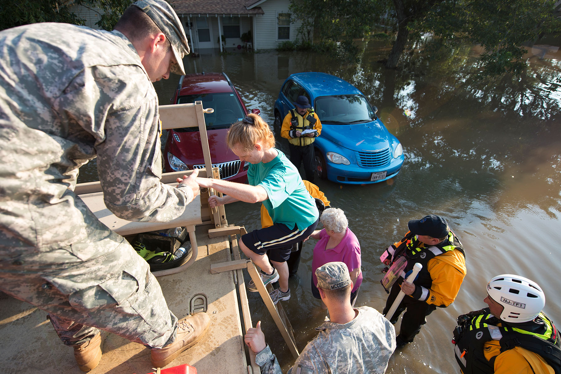 Staff Sgt. Class Richard Call, of the New Jersey National Guard, and members of New Jersey Task Force 1, assist evacuees into a Light Medium Tactical Vehicle (LMTV) to during water rescue operations in Wharton, Texas, Aug. 31, 2017. (Air National Guard/ Robert Shelley)