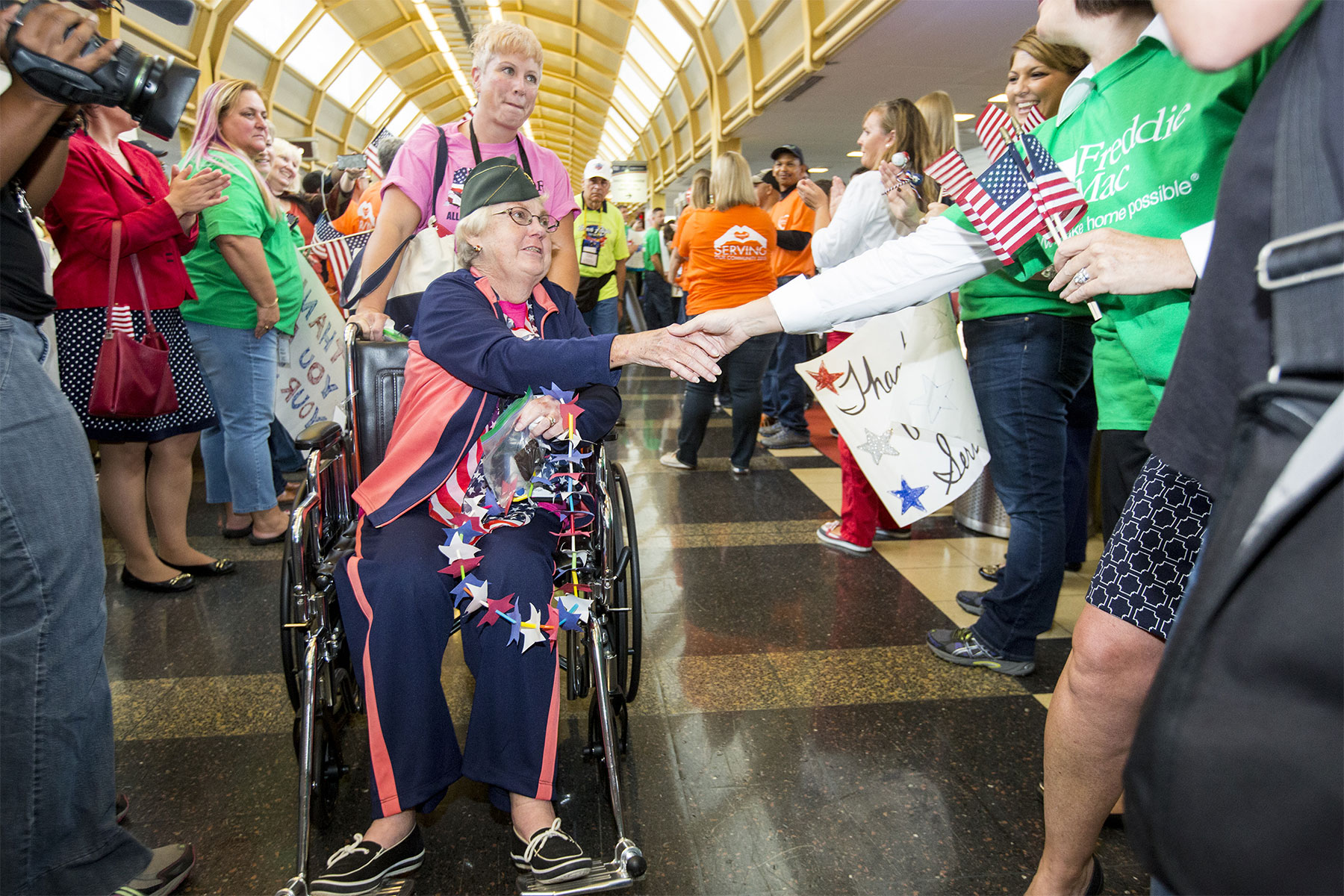 A veteran shakes the hand of one of over 400 supporters who greeted the first all-female honor flight in the United States Sept. 22, 2015 at Ronald Reagan International Airport in Arlington. Over 75 female veterans from World War II, the Korean War and the Vietnam War were in attendance, as well as 75 escorts, who were also female veterans or active-duty military. (U.S. Army/Nell King)