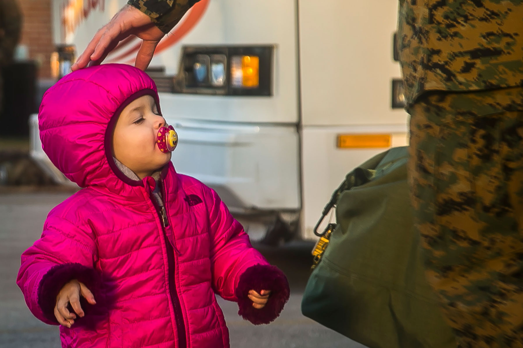 A child interacts with a U.S. Marine with the 26th Marine Expeditionary Unit (MEU), during the unit's departure from Camp Lejeune, N.C., to embark on a deployment at sea Feb. 6, 2018.  (U.S. Marine Corps)