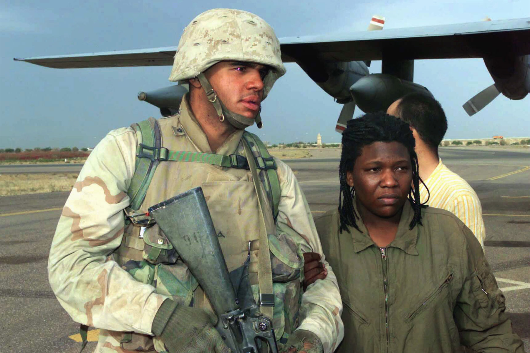 Lance Cpl. Curney Russell, from the 3rd Light Armored Reconnaissance Battalion, provides a steady arm for former prisoner of war Spc. Shoshana Johnson, with the 507th Maintenance Company, at Kuwait City, April 13, 2003, during Operation Iraqi Freedom. (U.S. Marine Corps/Michael Leitenberger)