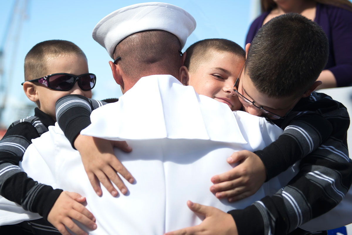 Sailor Embraces his Sons During Homecoming Celebration