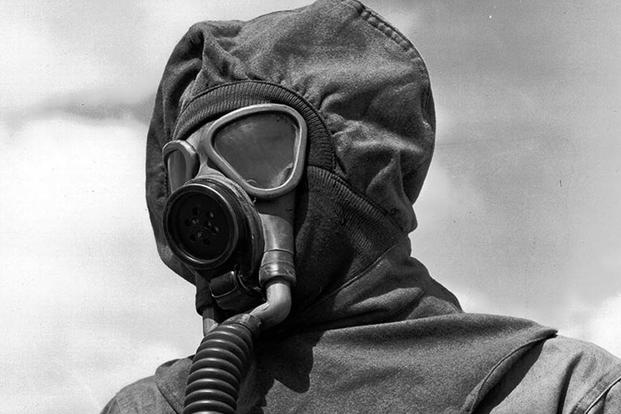 FILE -- Close-up of a soldier in gas mask and protective cloth permeable helmet at Chemical Warfare decontamination demonstration at Fort Bliss, Tx. (Sept. 7, 1944) (Signal Corps Photo via Center of Military History)