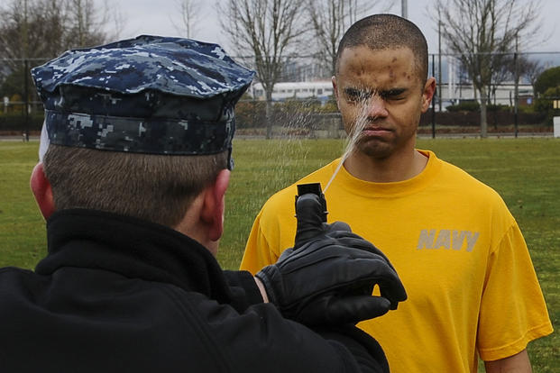 A sailor with the security department of the aircraft carrier USS Nimitz (CVN 68) is sprayed with pepper spray during a security academy qualification Feb. 8, 2013, at Naval Station Everett, Wash. (U.S. Navy photo/Chris Bartlett)