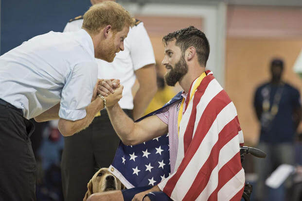 rince Harry shakes hands with Army veteran Sgt. Stefan Leroy while his dog looks on during swim finals at the Invictus Games in Toronto, Sept. 29, 2017. Prince Harry, who served in Afghanistan, established the games in 2014. (DoD/Roger L. Wollenberg)