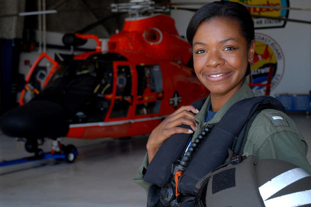 Lt. j.g. Lashanda Holmes stands in front of an MH-65 Dolphin helicopter at Air Station Los Angeles. (U.S. Coast Guard/ Adam Eggers)