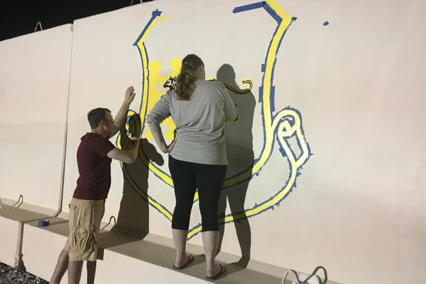 Tech. Sgt. Alison Haas and Airman First Class Matthew Sherbon paint a mural in late December 2017 at a base in Southwest Asia. (Photo by Hope Hodge Seck/Military.com)