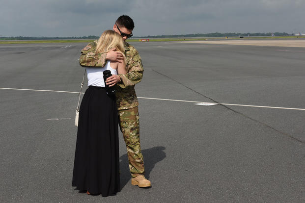 A deploying North Carolina Air National Guardsman hugs his wife and says goodbye before departure at the North Carolina Air National Guard Base, Charlotte Douglas International Airport. (Nathan Clark/U.S. Air Guard)