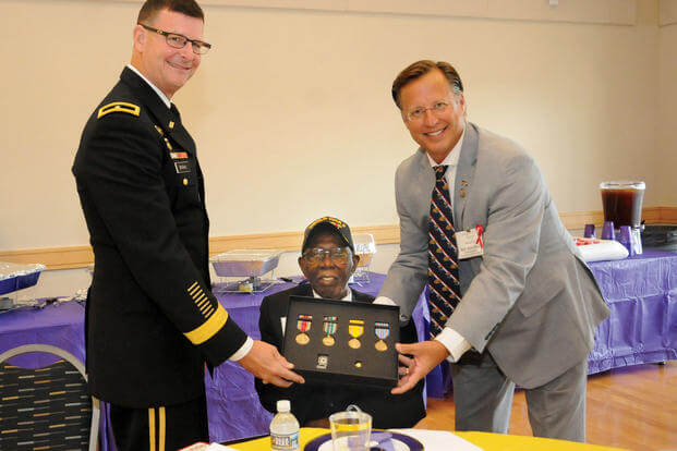 Congressman Dave Brat (right) along with Brig. Jeffrey Drushal, Chief of Transportation at Fort Lee, present the 99-year-old Richard Bell Jr. with his World War II medals during a family reunion event Aug. 26, 2017, at the Eastern Henrico Recreation Center. Bell's great nephew and former reporter Benjamin Sessoms Jr. discovered a year ago his relative never received awards pertaining to his military service and initiated efforts for a formal presentation. (U.S. Army/Terrance Bell)