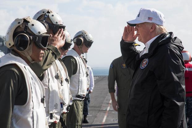 President Donald J. Trump, right, salutes Marines with the 26th Marine Expeditionary Unit, during his visit aboard the amphibious assault ship USS Kearsarge (LHD 3), Caribbean Sea, Oct. 3, 2017. (U.S. Marine Corps/Lance Cpl. Alexis C. Schneider)