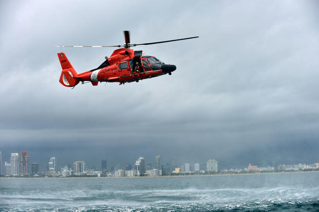 Petty Officer 3rd Class Bryan Evans, a Coast Guard Air Station Miami rescue swimmer, prepares for a free fall deployment from a MH-65 Dolphin helicopter east of Miami Beach on June 6, 2017. (Coast Guard photo/Eric D. Woodall)