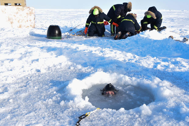 Chief Hospital Corpsman Kristopher Mandaro, assigned to Underwater Construction Team One (UCT 1), surfaces from a waterhole during a torpedo exercise in the Arctic Circle in support of Ice Exercise (ICEX) 2018, March 16. (U.S. Navy photo/Daniel Hinton)