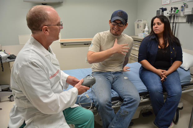 Army Col. Evan Renz explains the function of a vacuum-assisted closure device to Indalecio Morales while Morales' wife, Maribel, looks on in the U.S. Army Institute of Surgical Research Burn Center at San Antonio Military Medical Center. (U.S. Army/Lori Newman)