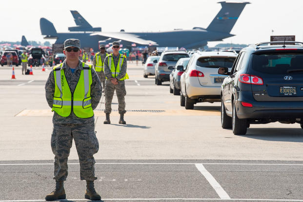 """Thunder Over Dover"" parking volunteers stand ready to direct incoming vehicles from the North Gate to parking spaces on the main flight line ramp Aug. 27, 2017, on Dover Air Force Base, Del. (U.S. Air Force photo/Roland Balik)"
