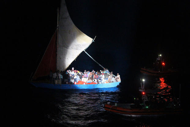 Two Coast Guard Cutter Reliance smallboat crews approach an overloaded 70-foot Haitian migrant sail freighter Saturday, April 7, 2018 approximately 30 miles northeast of Moa, Cuba. The cutter crew transferred 50 migrants to the Reliance and repatriated them the Haitian Coast Guard.  (U.S. Coast Guard photo)