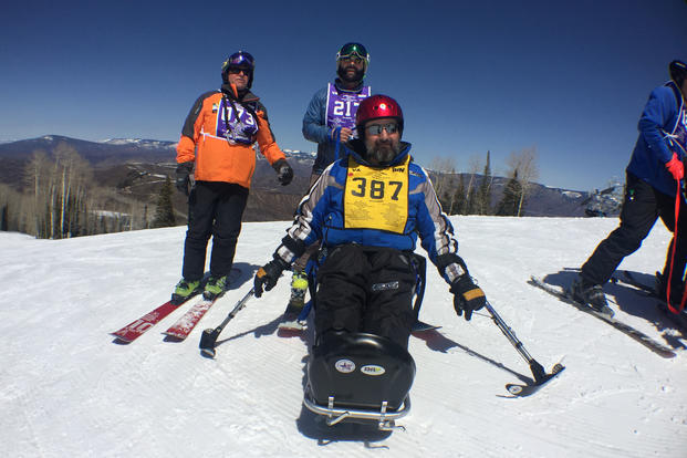 Volunteer ski instructor Alec Tossani (back row, in blue) poses with another instructor and Marine Corps veteran Patrick Ozborn as the trio tackle the slopes of Snowmass Mountain.
