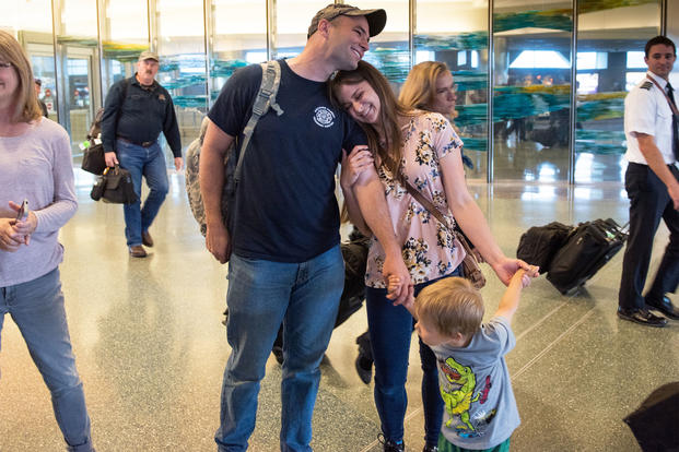 Spc. Joshua Monroe is greeted by his wife, son and friends and senior Idaho Army National Guard leadership, in Boise, Idaho. (Idaho National Guard/Robert Barney)