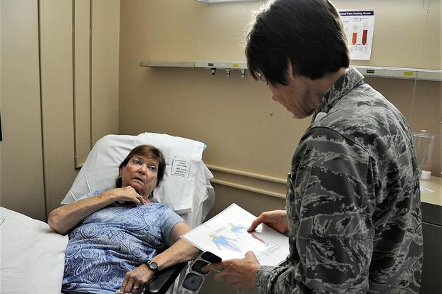 Lt. Col Candy Wilson (right), 779th Medical Group nurse practitioner, consults a human anatomy chart to determine where to place a Calmare electrode for treating Carol Celeste Gray, a Tricare beneficiary May 30, 2017 at Joint Base Andrews, Md. (U.S. Air Force photo by Staff Sgt. Joe Yanik)
