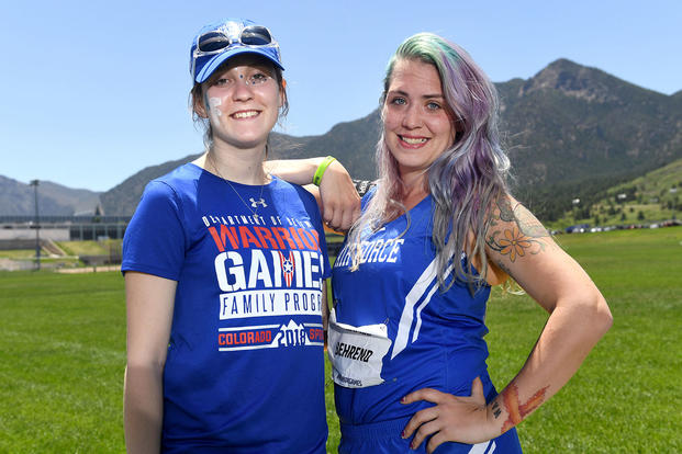 Medically retired Air Force Senior Airman Karah Behrend and her sister Crystal Boyd pose for a photo at 2018 Warrior Games at the Air Force Academy in Colorado Springs, Colo. June 2, 2018. The sisters met for the first time in person at the games. (DoD photo/EJ Hersom)