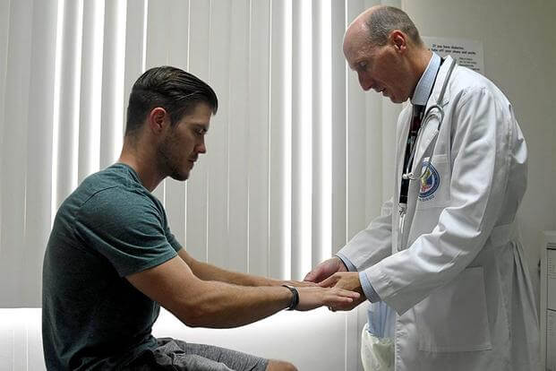 Doctor checks the hands of a patient. (Image: Department of Veterans Affairs)
