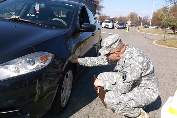 Sgt. 1st Class Raymond M. Richardson, a kennel master with the 289th Military Police Company, checks the tire tread on a car during a safety inspection of the vehicles of Soldiers assigned to the company Nov. 24, 2014. (Julia LeDoux/U.S. Army)