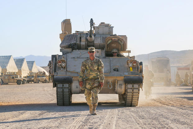 A U.S. Army Soldier assigned to 3rd Armored Brigade Combat Team, 1st Armored Division, Fort Bliss, Texas, ground guides an M2 Bradley Infantry Fighting Vehicle out of the Rotational Unit Bivouac Area prior to rollout during Decisive Action Rotation 18-08 at the National Training Center, Fort Irwin, Calif., June 1, 2018. (U.S. Army photo/Esmeralda Cervantes)