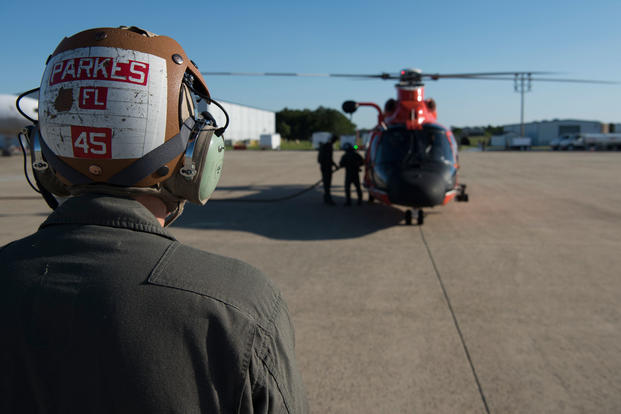 U.S. Marine Corps Sgt. Robert Parkes, Marine Medium Tilt Roader Squadron (VMM) 774 V-22 crew chief, poses in front of a U.S. Coast Guard Air Station Atlantic City HH-65 Dolphin on Coast Guard Air Station Atlantic City, N.J., June 14, 2018. The Marines conducted a forward air-refueling point for the first time – refueling an HH-65 with a VMM-774 V-22 Osprey. (U.S. Air Force photo/Ariel Owings)