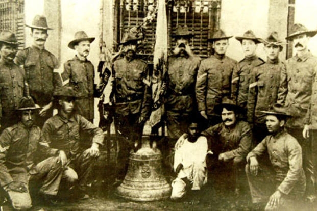 Soldiers from the 9th Infantry Regiment pose with one of three Balangiga bells in the Philippines in 1902 in this photo, displayed at the 2nd Infantry Division museum.