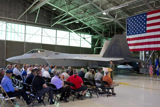 Lt. Col. Lee Bryant addresses base leadership along with Lockheed Martin and Boeing representatives, to welcome back to life Raptor # 91-4006, which has been on the ground for almost six years. (Courtesy photo by Christopher Higgins/Lockheed Martin)
