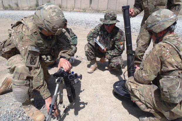 U.S. Army Sgt. Eric Chaffins and Spc. Richard Cazarez explain the set up and use of an M224 60 mm mortar system with bipod to Afghan National Army 1st Lt. Isaqh in Paktika province, Afghanistan, June 12, 2013. (U.S. Army courtesy photo)