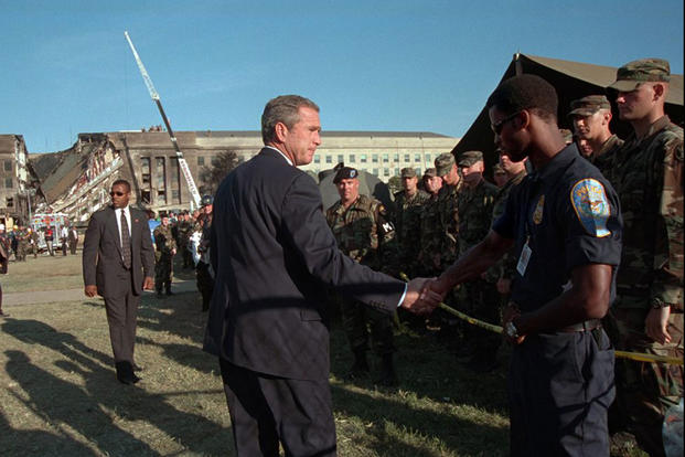 President George W. Bush greets rescue workers, firefighters and military personnel, Sept. 12, 2001, while surveying damage caused by the previous day's terrorist attacks on the Pentagon. (Photo by Eric Draper, Courtesy of the George W. Bush Presidential Library)