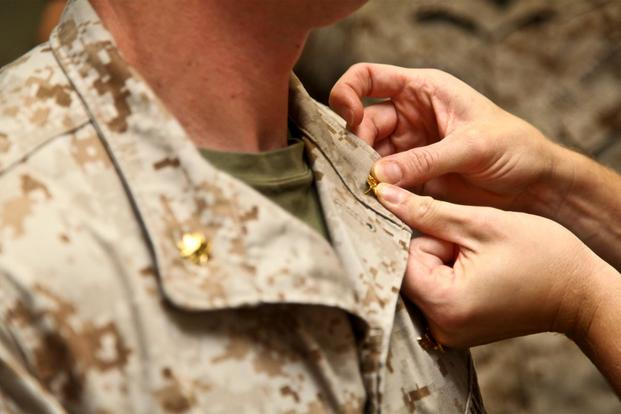 A Marine major is pinned with his new rank during a promotion ceremony in 2014. More officers could join the sea services at higher ranks as leaders look to attract those in technical fields, such as cyber. (Cpl. Emmanuel Ramos/Marine Corps)