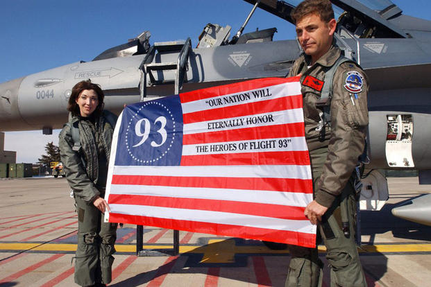 Sandra Dahl, left, is the widow of Jason Dahl, the pilot of United Airlines Flight 93, which went down in Somerset, Pennsylvania, on Sept. 11, 2001. The plane was believed to have been en route to the White House. Here, she holds an American flag along with Air Force Lt. Col. Mike Low after flying in the back seat of his F-16 Fighting Falcon fighter. (Air Force photo by Tech Sgt. Darin Overstreet)