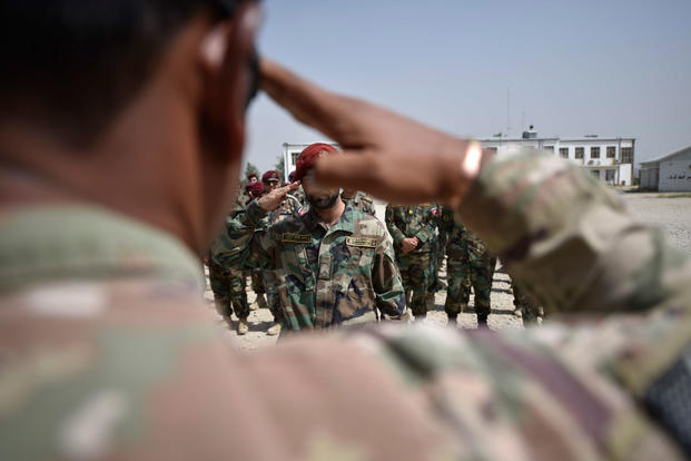 An Afghan National Army Special Operation Commando, General Support Kandak (GSK) Commando salutes his U.S. Army mentor before stepping forward to receive his Commando Basic Leadership Course graduation certificate during a ceremony held near Kabul, Afghanistan, August 16, 2018. (NATO photo/Felix Figueroa)