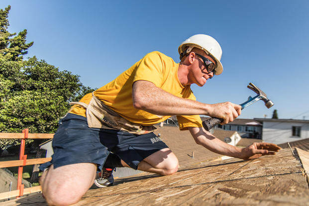 Boatswains mate Zach Lee, USS Anchorage (LPD 23), hammers nails into the roof of a house during a Habitat for Humanity neighborhood rebuild project in Long Beach, California during Los Angeles Fleet Week. (U.S. Marine Corps/Gunnery Sgt. Robert Brown)