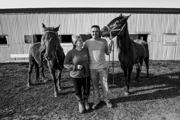 Tiffany Wisley, Langley Saddle Club head feeder, and U.S. Air Force Staff Sgt. Cody Wisley, 83rd Network Operations Squadron boundary protection supervisor, pose for a photo with their horses Spooks and Steel at the stables on Joint Base Langley-Eustis, Virginia. (U.S. Air Force/Areca T. Bell)