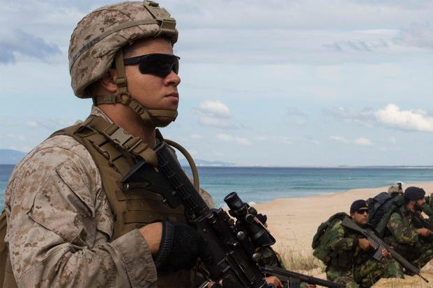 A U.S. Marine with the 26th Marine Expeditionary Unit holds security with Portuguese Marines at Praia Da Raposa beach in Portugal, during NATO's Trident Juncture exercise in October 2015. (US Army photo/Austin Long)