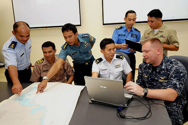 June 2011:  Cmdr. Troy Amundson (far right) joins liaison officers from (left to right) Brunei, Thailand, Indonesia, Singapore, Malaysia and the Philippines for training at Singapore's Changi Naval Base. (Photo courtesy of Singapore Ministry of Defense)