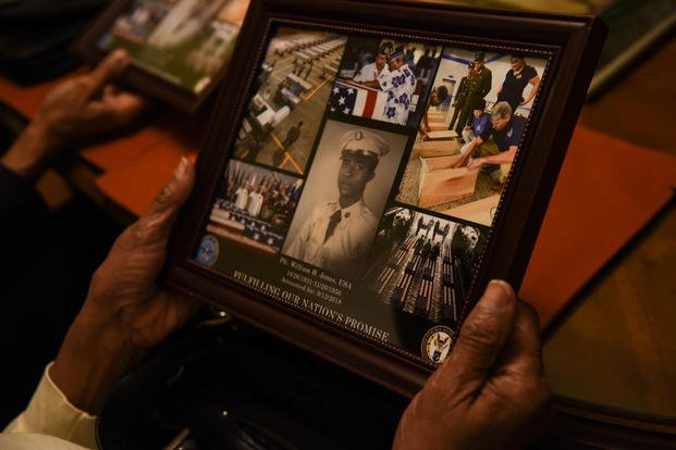 Ida Jones-Dickens holds a collage at her sister's home in Rocky Mount, North Carolina, Nov. 15, 2018. (U.S. Air Force photo by Staff Sgt. Apryl Hall)