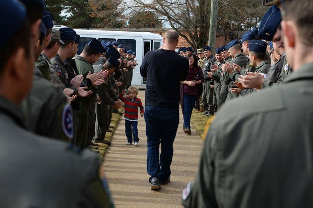 Pilots from the 41st Flying Training Squadron welcome Tobias Taylor, Pilot for a Day, and his family, Dec. 6, 2018, on Columbus Air Force Base, Mississippi. (U.S. Air Force/Hannah Beam)