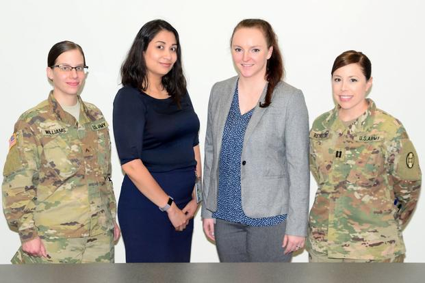 U.S. Army Cpl. Samantha Williams, a paralegal, Aracely Lopez and Evelyn Saxton, both lawyers, and U.S. Army Capt. Katie Reynolds, the site coordinator, pose at the North Carolina National Guard Headquarters Judge Advocate courtroom at NCNG headquarters in Raleigh, North Carolina, May, 3, 2019. The team of legal experts through the IRS Volunteer Income Tax Assistance program prepared and filed more than 550 state and federal tax returns from January to April this year for service members, retirees and their