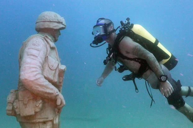 Shawn Campbell, a former staff sergeant and now a master diver, admires the detail of one of the statues at the Circle of Heroes underwater veterans memorial off the coast of Clearwater, Fla. (U.S. Army/Video still by Bill Mills)