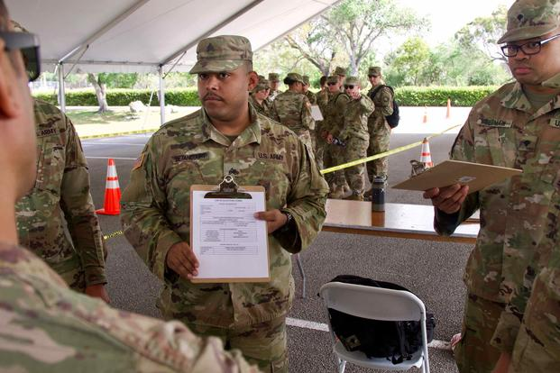Florida National Guard Sgt. Jeff Betancourt reviews the scripting process with medics at a COVID-19 testing site.