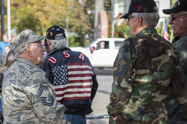 Two veterans talk with each other during the Yuba-Sutter Veterans Day Parade in Marysville, California,