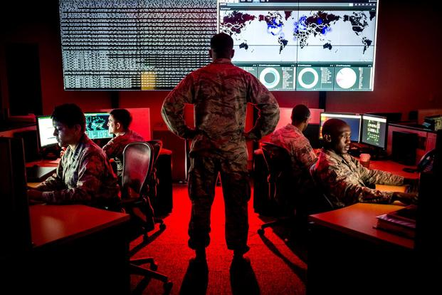 A cyber warfare operations officer watches service members analyze log files at Warfield Air National Guard Base.