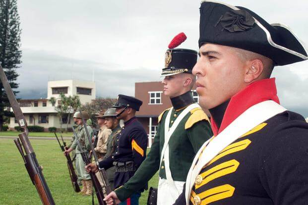 Marines and sailors stand in formation dressed up in historical uniforms.
