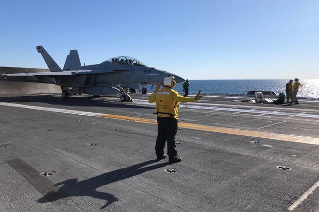 A crew member signals to an F/A-18 Super Hornet preparing for launch on the deck of the carrier Gerald R. Ford Nov. 17, 2020 (Hope Hodge Seck/Staff)
