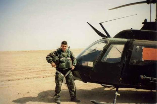 Fred Wellman stands next to his Kiowa OH-58C.