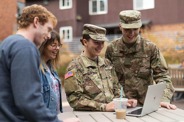 Military members look at laptop