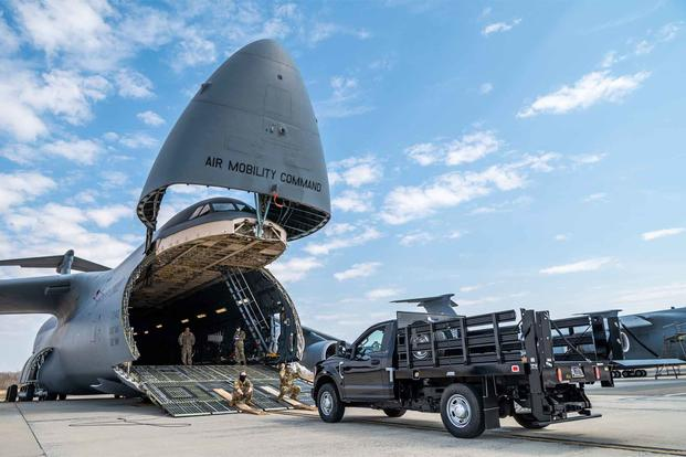 Airmen load a truck onto a C-5M Super Galaxy.